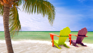Panorama of colorful lounge chairs at a tropical paradise beach in Miami Florida. Beautiful aqua green waters of the ocean hanging palm tree branches and a blue sky in the background